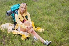 Full length of thoughtful female hiker sitting on grass Stock Photo