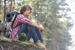 Full length of thoughtful male backpacker relaxing on cliff in forest Royalty Free Stock Photo