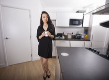 Full length of thoughtful young holding coffee mug in kitchen Royalty Free Stock Photos