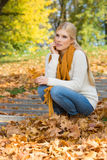 Full length of thoughtful young woman crouching on steps in park Stock Photography
