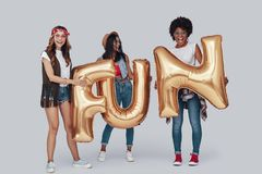 Full length of three attractive young women. Carrying balloons and smiling while standing against grey background stock photo