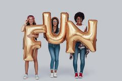 Full length of three attractive young women. Carrying balloons and smiling while standing against grey background royalty free stock images