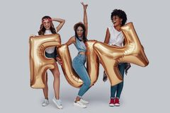 Full length of three attractive young women. Full length of three attractive young woman carrying balloons and smiling while standing against grey background stock photography