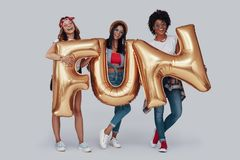 Full length of three attractive young women. Carrying balloons and smiling while standing against grey background stock photos