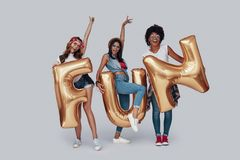 Full length of three attractive young women. Gesturing and smiling while standing against grey background royalty free stock photography