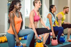 Three young people holding kettlebells during functional training royalty free stock photography