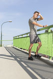 Full length of tired man wiping sweat on bridge after jogging Stock Photography