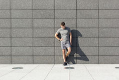 Full length of tired sporty man leaning on tiled wall Stock Images