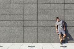 Full length of tired sporty man leaning on tiled wall Royalty Free Stock Images
