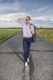 Full length of tired young man walking alone on rural road Royalty Free Stock Photography