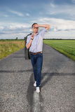 Full length of tired young man walking alone on rural road Stock Images