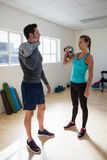Full length of trainer with female athlete lifting kettlebells. In gym Stock Image