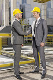Full length of two architects greeting on construction site Royalty Free Stock Images