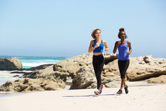 Full length two young women running on the beach Royalty Free Stock Image