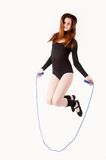 Fitness woman with jumping rope. Full length view of an attractive woman with jumping rope at white background Royalty Free Stock Image