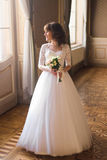 Full length view of beautiful woman posing in wedding dress near window at luxury interior Stock Photography