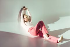 Full length view of beautiful young woman. In pink clothes lying in studio on grey stock photography