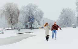 Full-length view of the cheerful laughing couple holding hands during their walk along the snowy landscape. Full-length view of the cheerful laughing couple Stock Photo