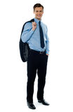 Full length view of a corporate young ceo. Portait of a professional businessman holding his coat and posing in style Royalty Free Stock Photo