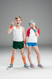 Full length view of cute smiling boy and girl in sportswear standing together and gesturing isolated on grey. Children sport concept Stock Images