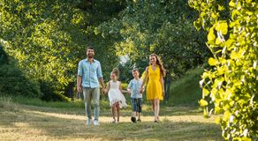 Happy family with two children holding hands during recreational walk. Full length view of a happy family with two children wearing casual summer clothes while Royalty Free Stock Photos