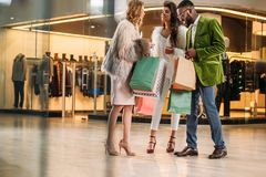 full length view of happy stylish multiethnic people looking into shopping bags stock images