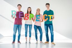 Friends holding word respect. Full length view of happy young friends holding colorful word respect and smiling at camera on grey Stock Image