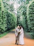 The full-length view of the kissing newlyweds and walking through the high bushes. The full-length view of the kissing newlyweds and walking through the high royalty free stock photography