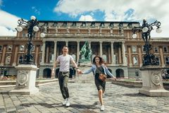 Full-length view of the pretty young couple in love holding hands while walking along the countryard at the Buda Castle. Royal Palace in Budapest, Hungary royalty free stock photography