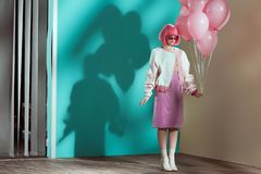 Full length view of stylish pretty girl. In bright wig holding pink balloons royalty free stock photo