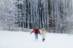 Full-length view of the two happy lovers are holding hands and cheerfully running along the snowy forest during the Stock Photography