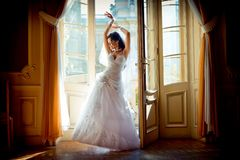 Full-length view of the young attractive charming bride in the gorgeous wedding dress posing near the window of the old royalty free stock photo