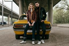 Full length view of young couple in leather jackets sitting on yellow old-fashioned car and looking. At camera stock photography