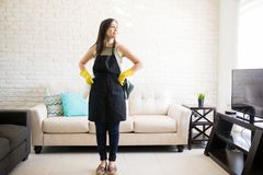 Young woman in living room with spray and rug looking away. Full length view of young maid in black apron and gloves standing in middle of living room looking Royalty Free Stock Image