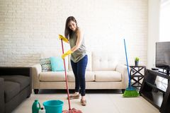 Happy housewife mopping floor with red mop and disinfectant. Full length view of young woman cleaning living room area with mop and broom Royalty Free Stock Images