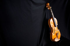 Full length violin leaning on black backdrop Royalty Free Stock Photography