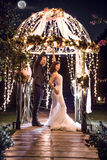 Full length of wedding couple dancing in illuminated gazebo at night Royalty Free Stock Images