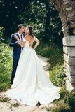 Full-length wedding portrait of the groom tenderly kissing his lovely bride with open back in cheek in the green forest Stock Photo
