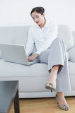 Full length of a well dressed woman using laptop on sofa Royalty Free Stock Photo