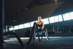 Full length wide angle shot of a young woman working out with battle ropes. royalty free stock photography