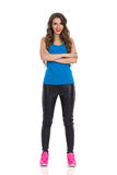 Full Length Woman With Crossed Arms. Smiling young woman in blue shirt, black leather trousers, and pink sneakers standing with arms crossed and looking at Stock Photos