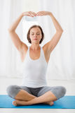 Full length of woman doing yoga. Full length of woman with eyes closed doing yoga at fitness studio stock images