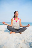 Full length of woman with eyes closed meditating at beach Stock Photo
