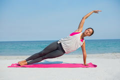 Full length of woman with eyes closed practicing yoga at beach Stock Images
