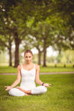 Full length of woman with eyes closed while sitting in lotus pose Stock Image