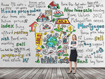 Full length woman in formal clothes holds a black folder. Colourful 'home sales' icons are drawn on the concrete wall. R Royalty Free Stock Images