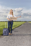 Full length of woman hitching while holding anywhere sign on country road Royalty Free Stock Images