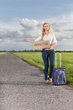 Full length of woman hitching while holding anywhere sign on country road Royalty Free Stock Image