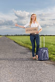 Full length of woman hitching while holding anywhere sign on countryside Royalty Free Stock Photography