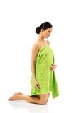 Full length woman kneeling wrapped in towel Royalty Free Stock Image